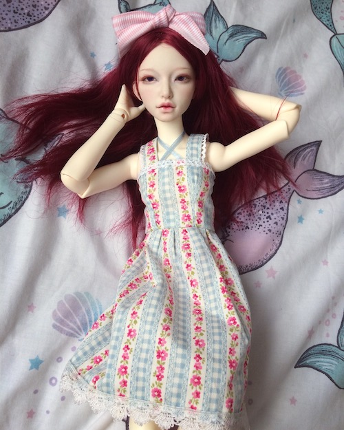 Eden laying in gingham rose dress