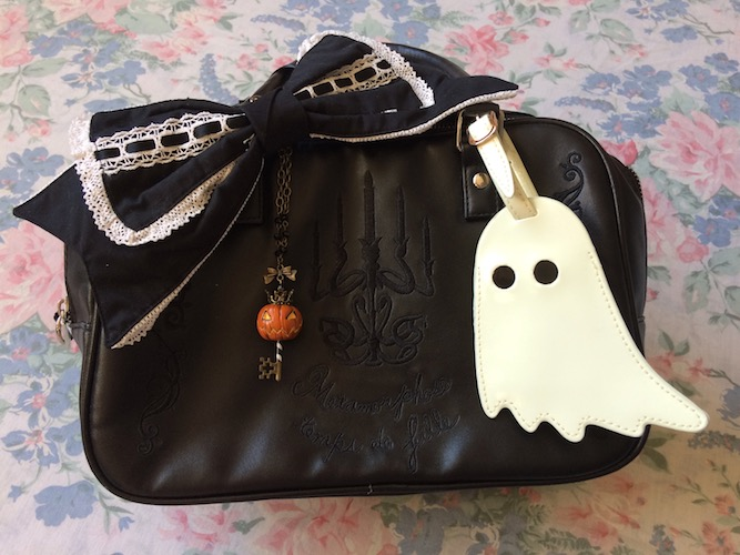 black bag, black bow, pumpkin necklace and white ghost